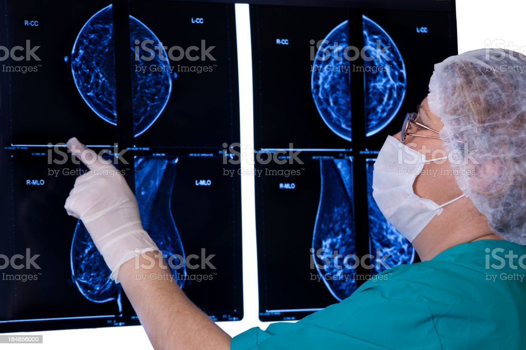 Doctor in scrubs and mask looking at results of MRI scan stock photo