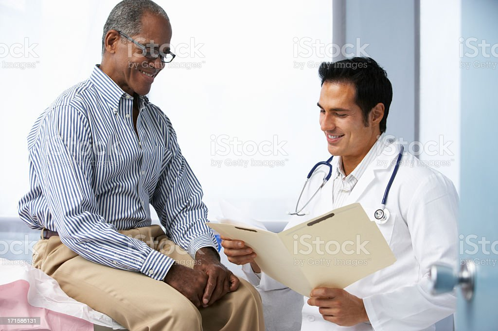 Doctor In Surgery With Male Patient Reading Notes royalty-free stock photo