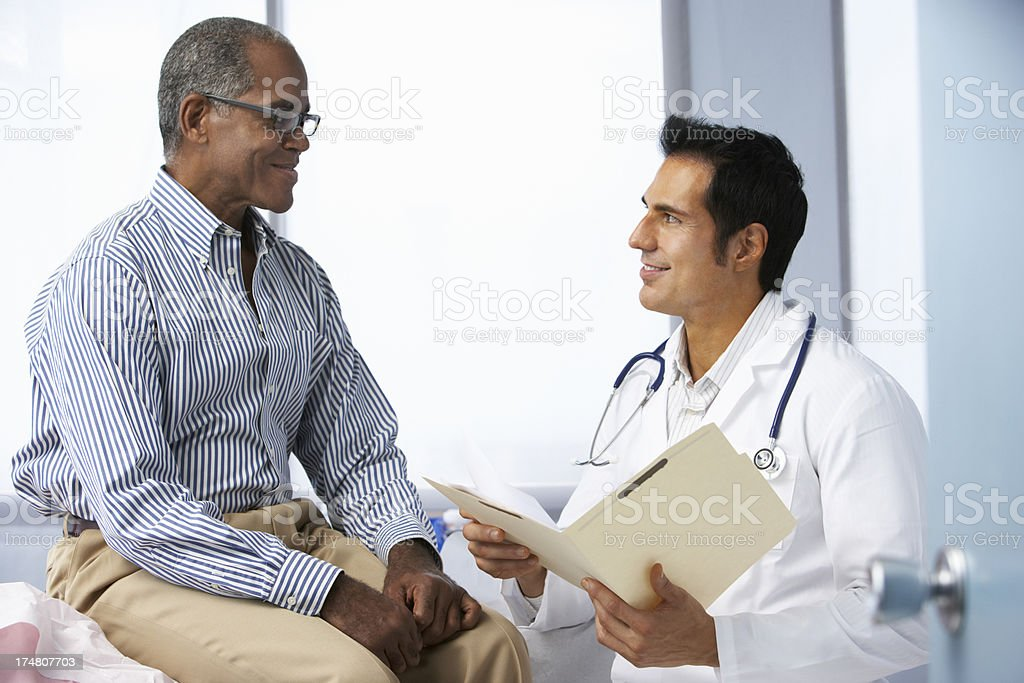 Doctor In Surgery With Male Patient Reading Notes stock photo