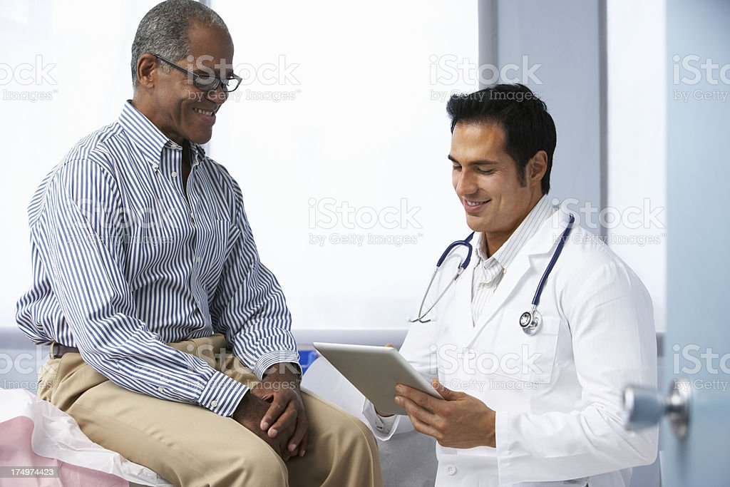 Doctor In Surgery With Male Patient Using Digital Tablet royalty-free stock photo
