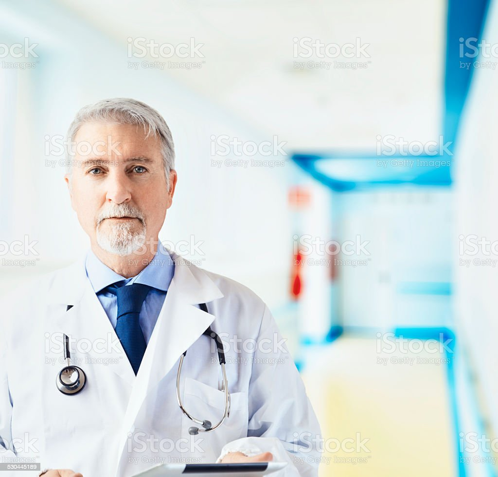 Doctor in the hospital hallway with tablet stock photo