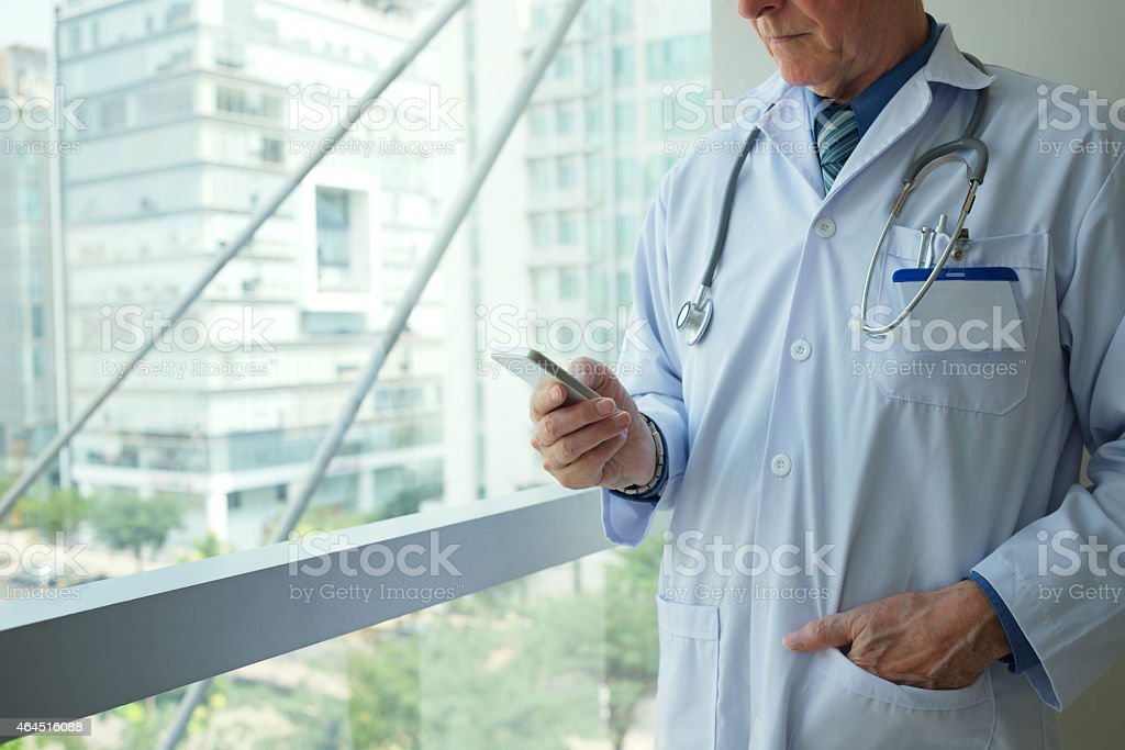 A doctor in uniform using a smartphone stock photo