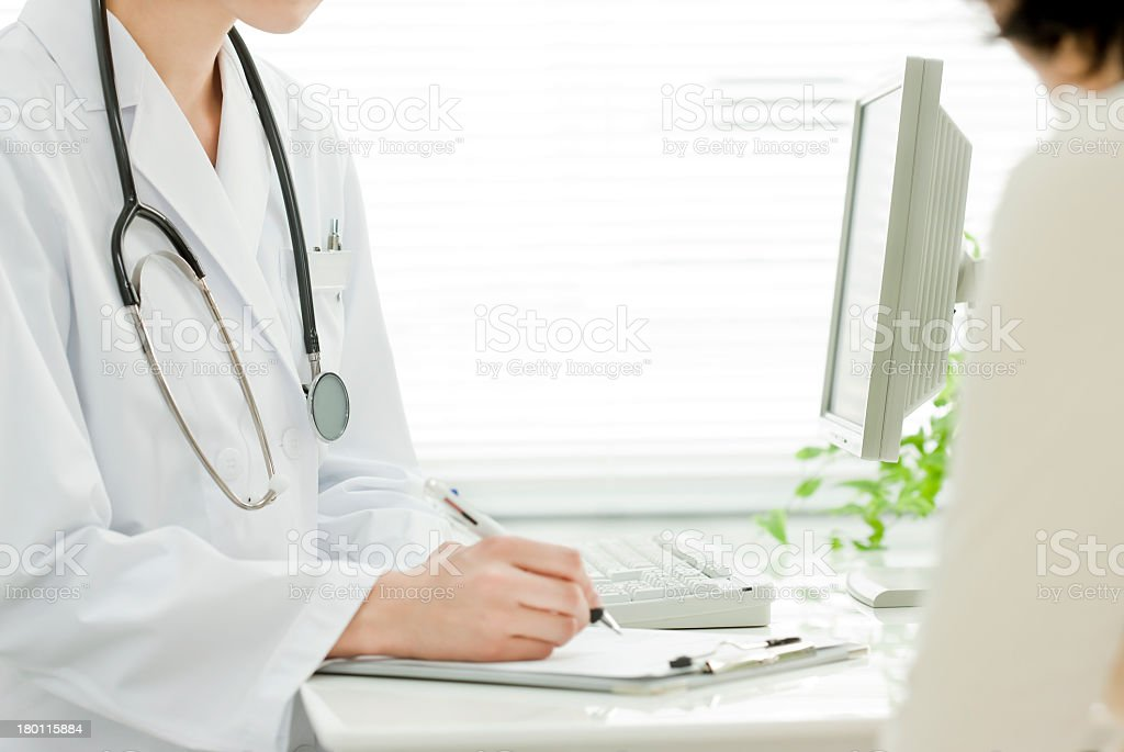 Doctor in white coat with stethoscope filling out forms stock photo