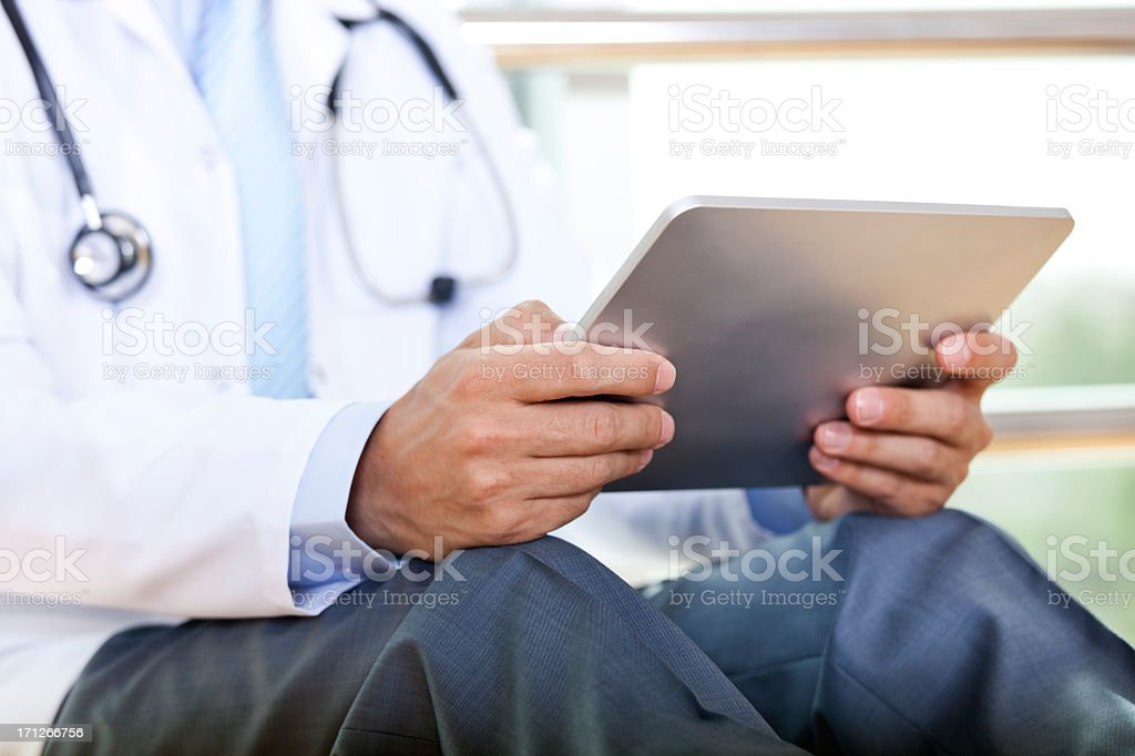 Doctor in white jacket and stethoscope reads from tablet stock photo