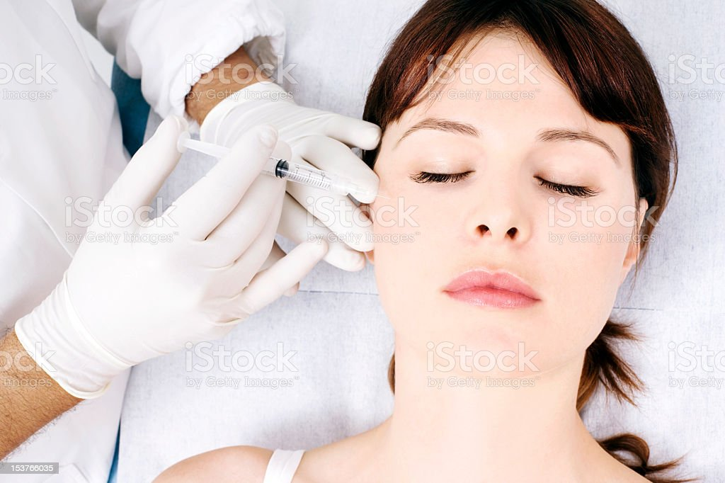Doctor injecting Botox into a woman's cheek stock photo