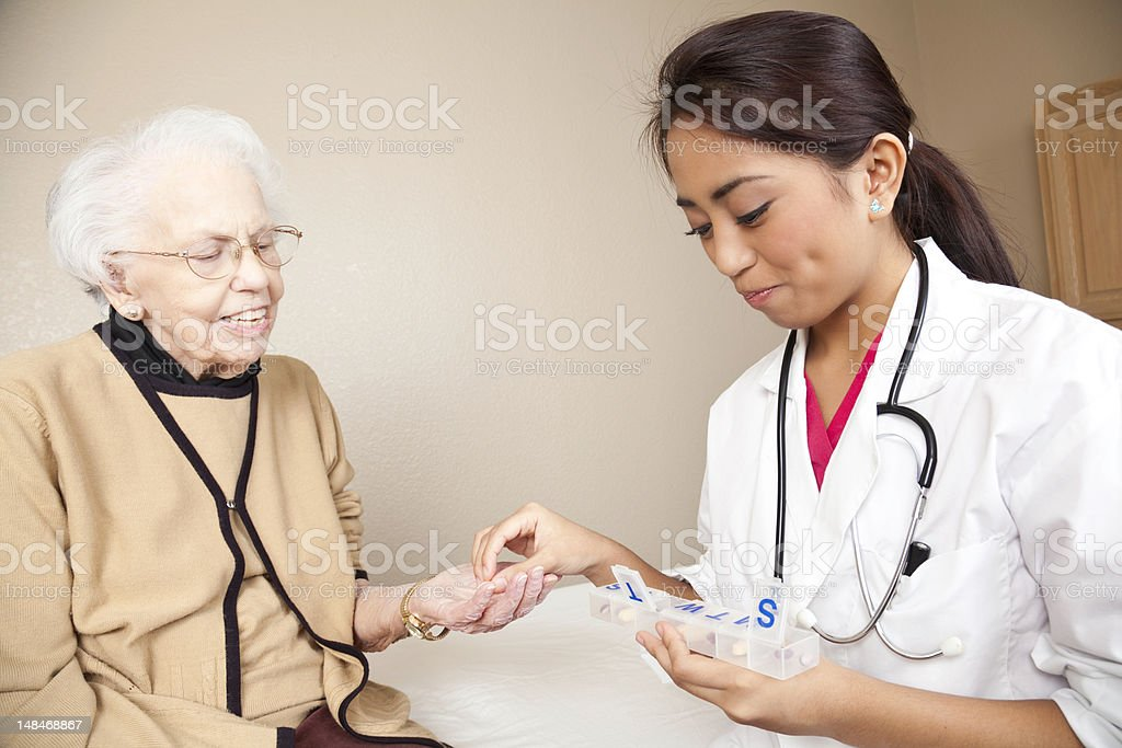 Doctor Instructing Senior Adult Patient on Medication Requirements royalty-free stock photo