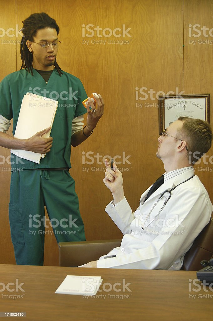 Doctor Instructs Nurse stock photo