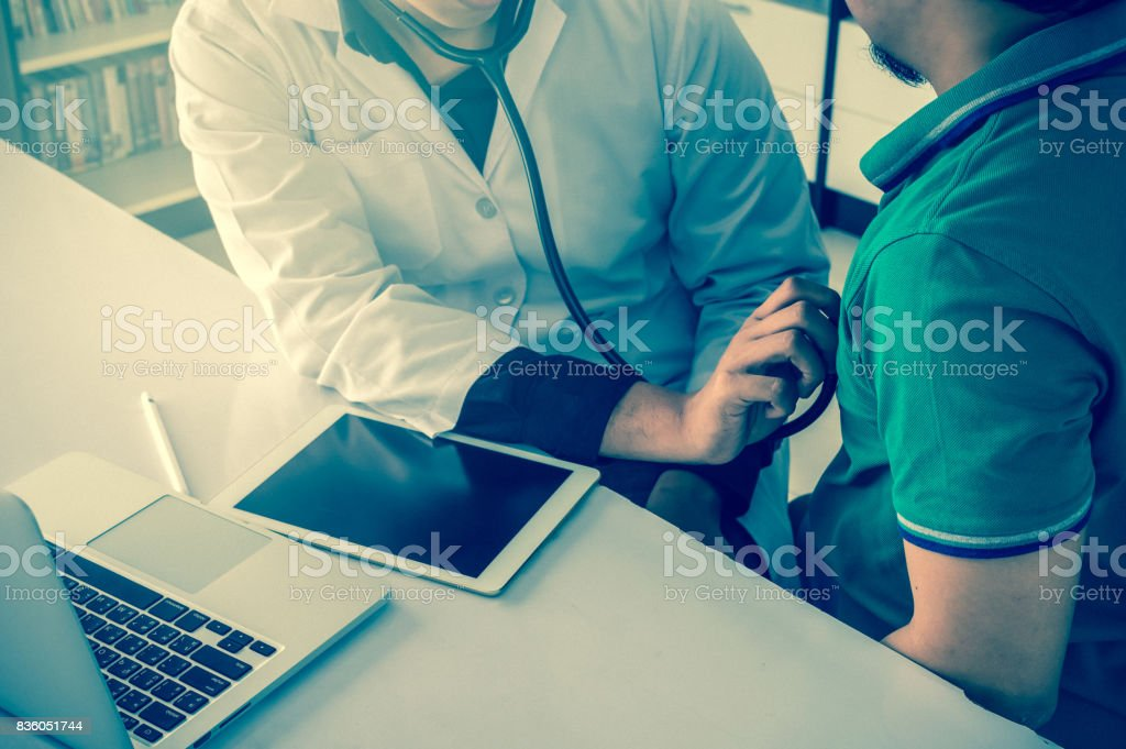 Doctor is consulting with Patient about his health on working desk which using technology tablet at hospital, physician concept stock photo