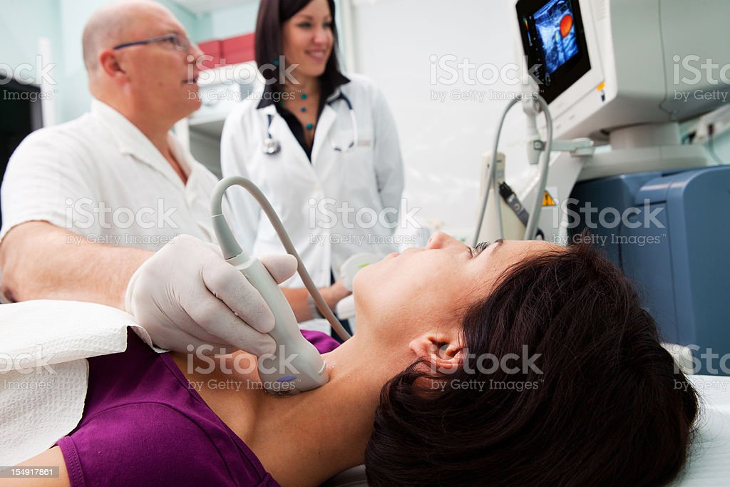 Doctor is giving beautiful young patient an ultra sound stock photo