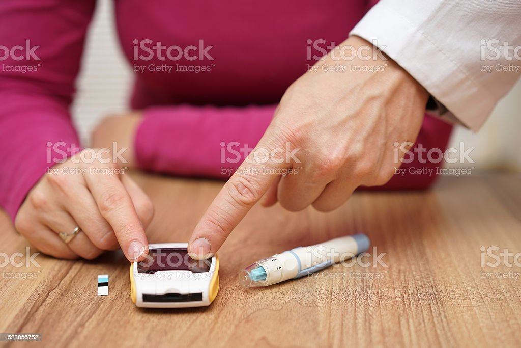 doctor is instructing how to use tester  for blood sugar stock photo