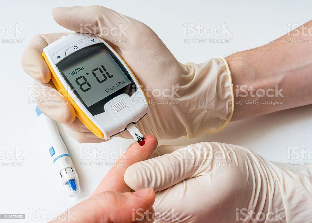 Doctor is measuring glucose level from blood of his patient. stock photo