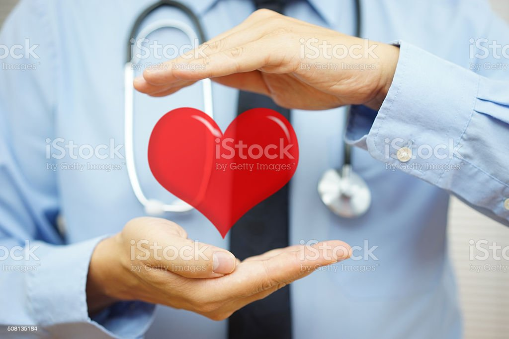 doctor is protecting heart  with hands. Cardiovascular diseases  concept stock photo