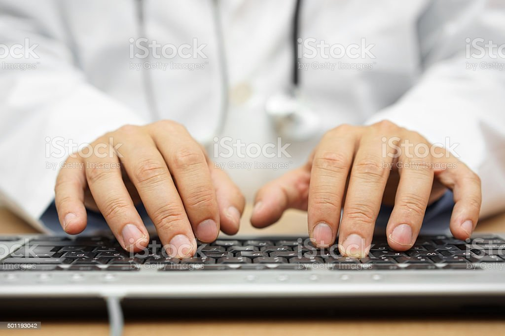 doctor is writing report into patient folder stock photo