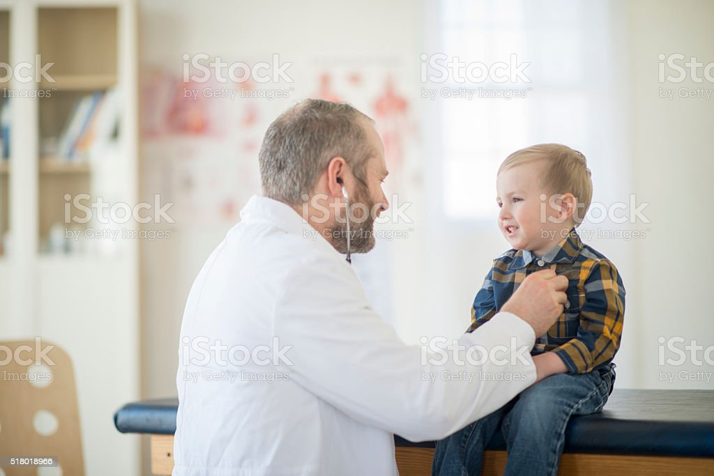Doctor Listening to a Child's Heartbeat stock photo