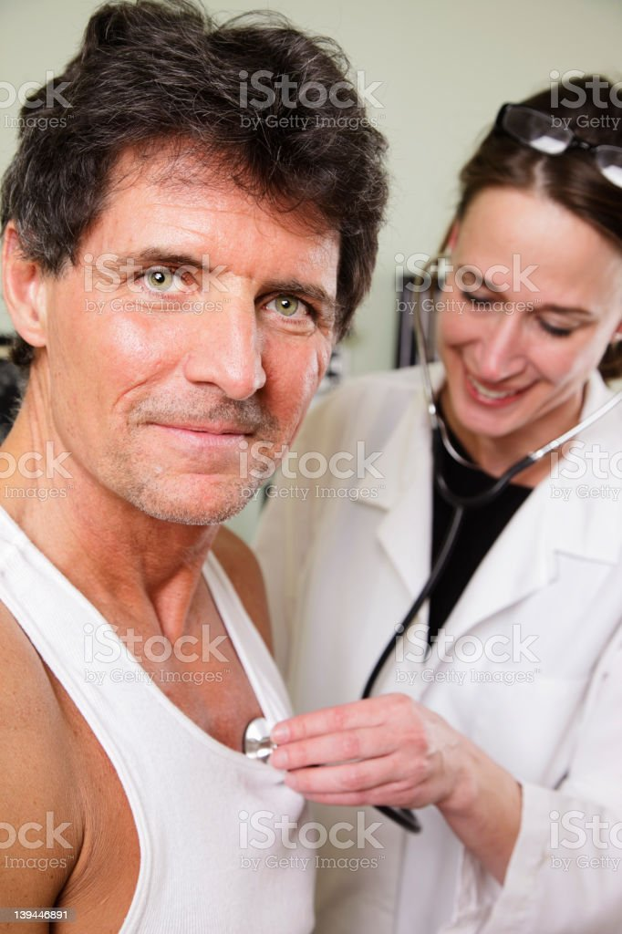 Doctor Listening to Heartbeat stock photo