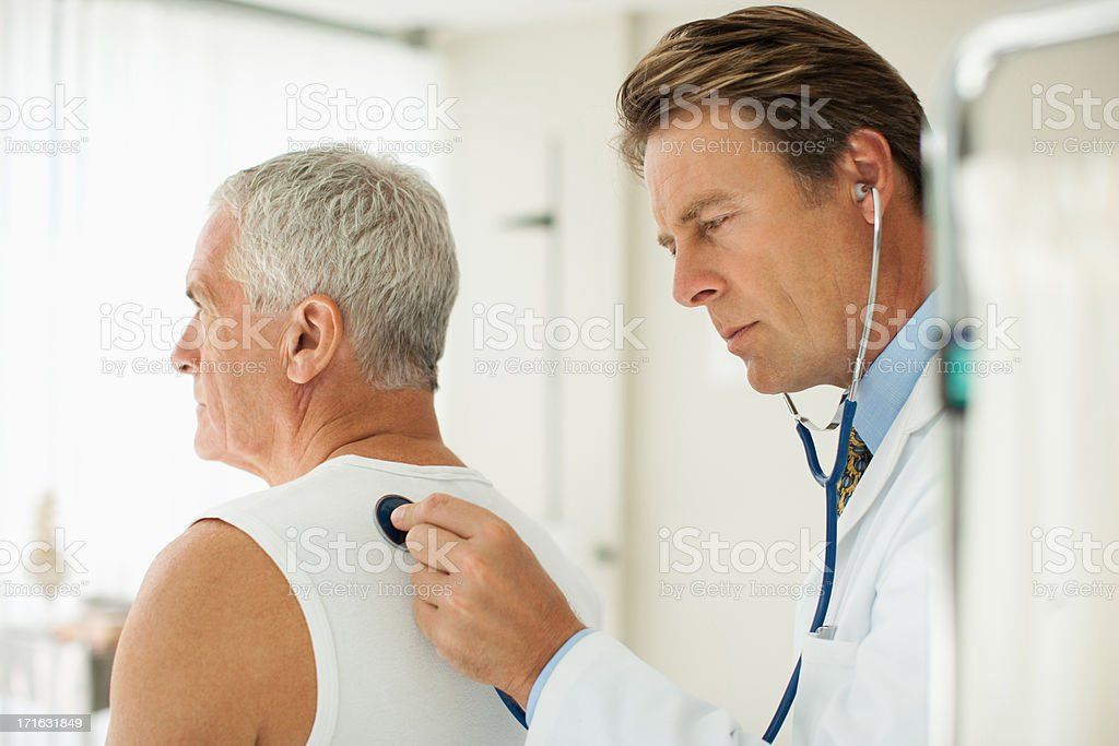 Doctor listening to man's breathing in doctor's office stock photo