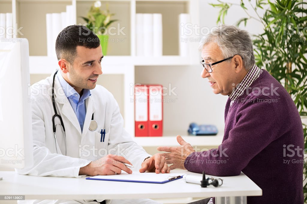 Doctor listening to patient explaining his painful stock photo