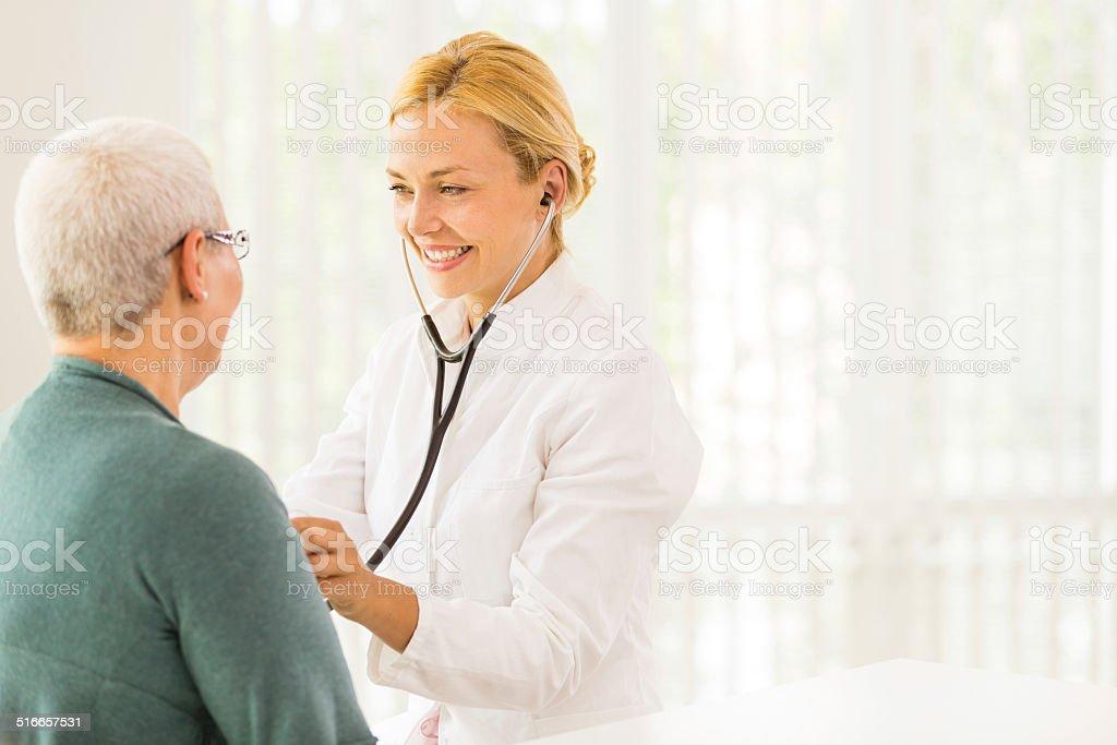 Doctor listening to senior patient's heart stock photo