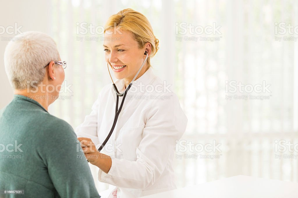 Doctor listening to senior patient's heart stock photo
