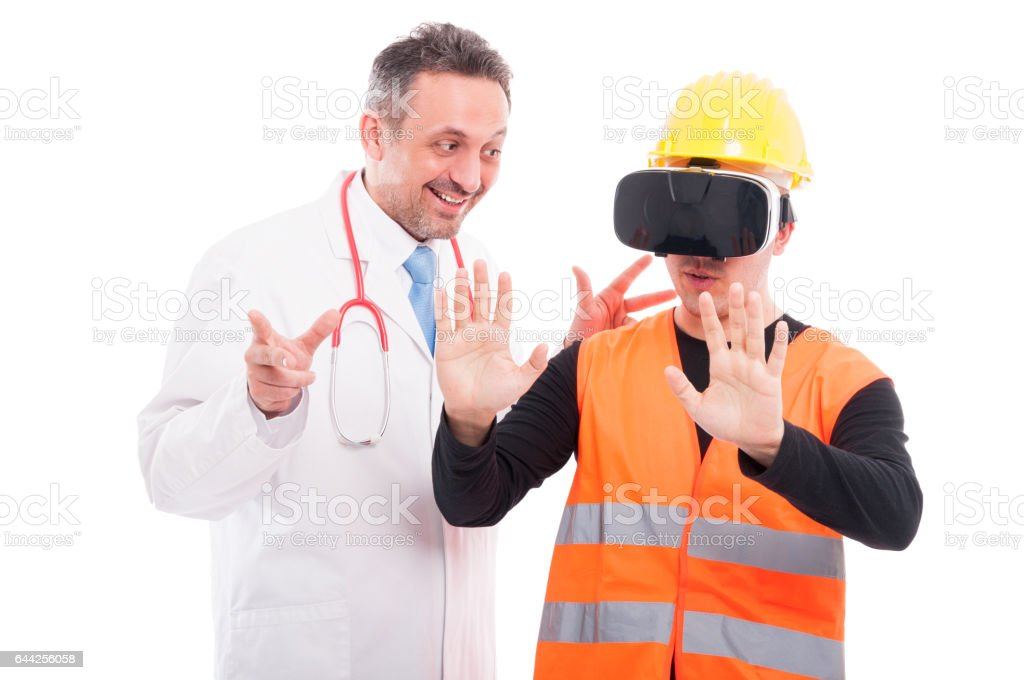 Doctor looking at constructor trying virtual reality glasses stock photo