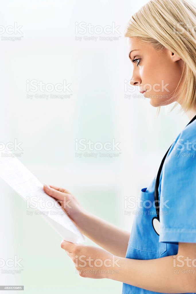 Doctor looking at medical chart. stock photo