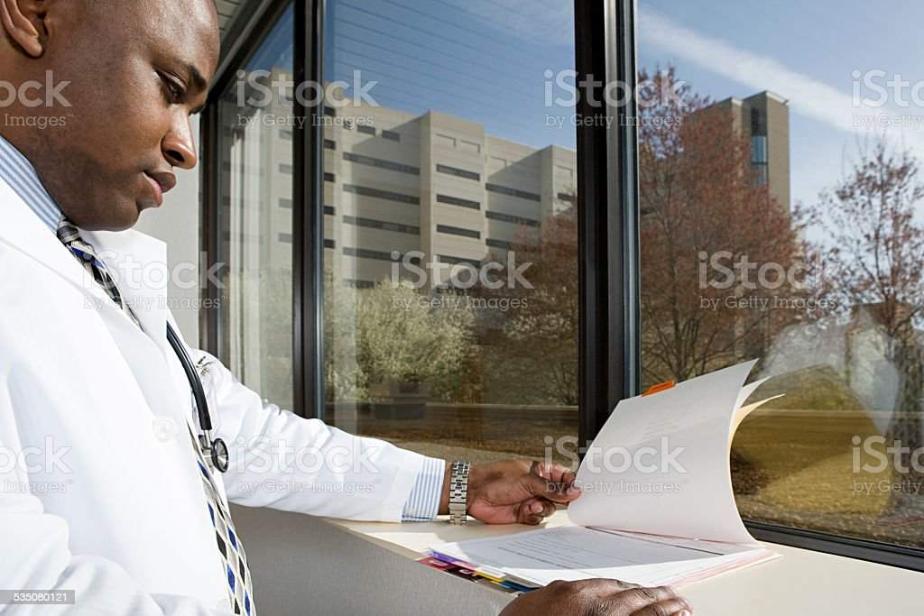 Doctor looking at paperwork stock photo