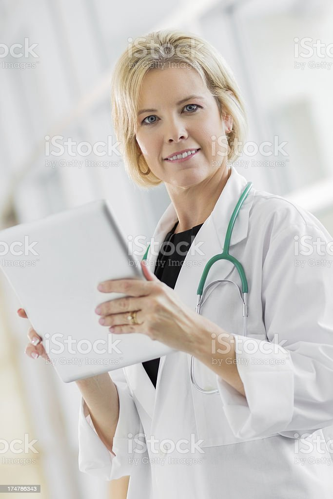 Doctor looking at patient records on a digital tablet stock photo