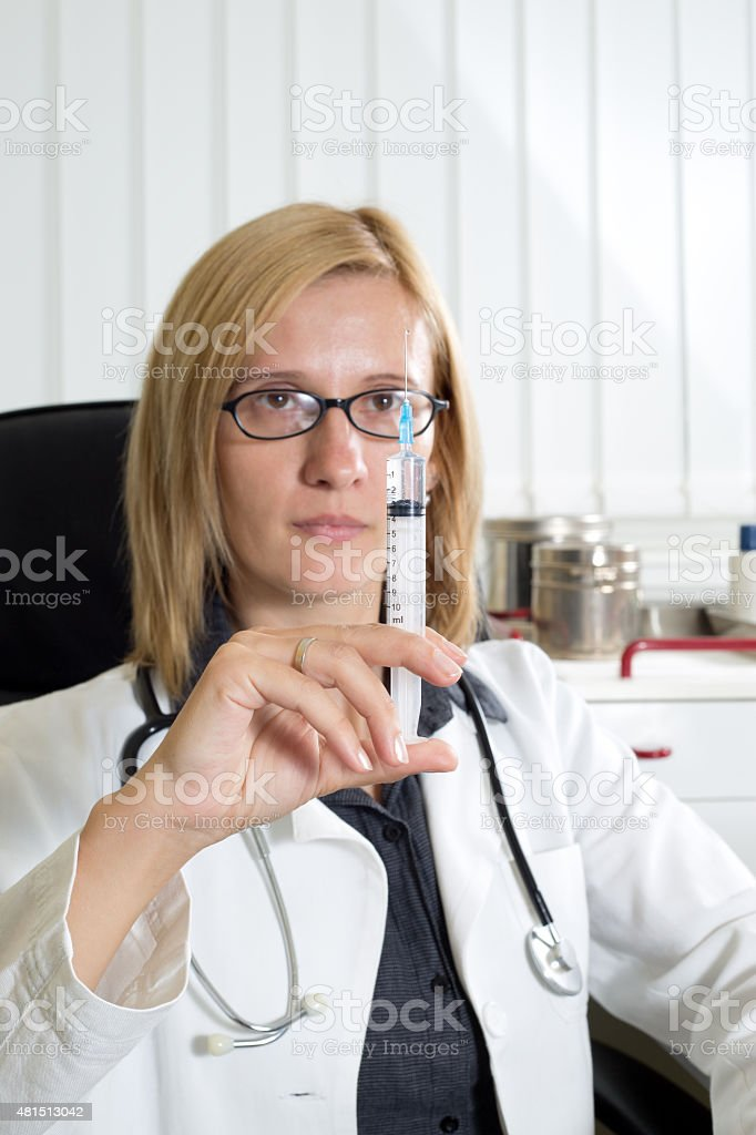 Doctor Looking at Syringe in Her Hand in Consulting Room stock photo