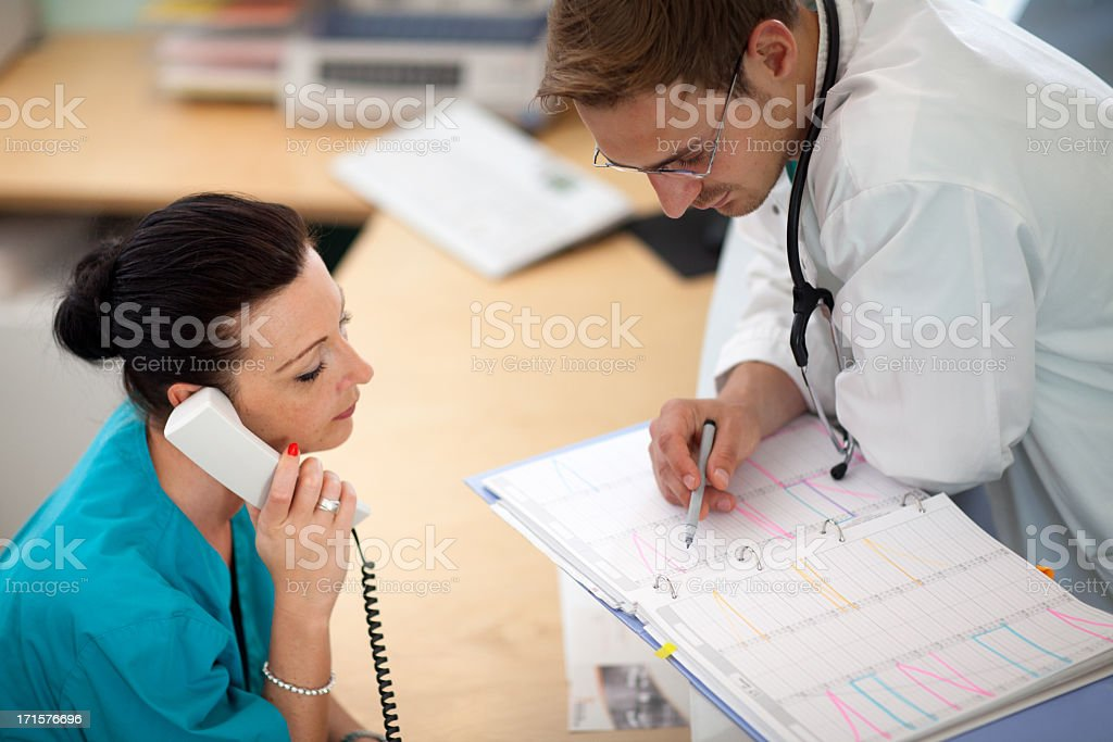doctor looks into organizer while nurse is at the phone stock photo