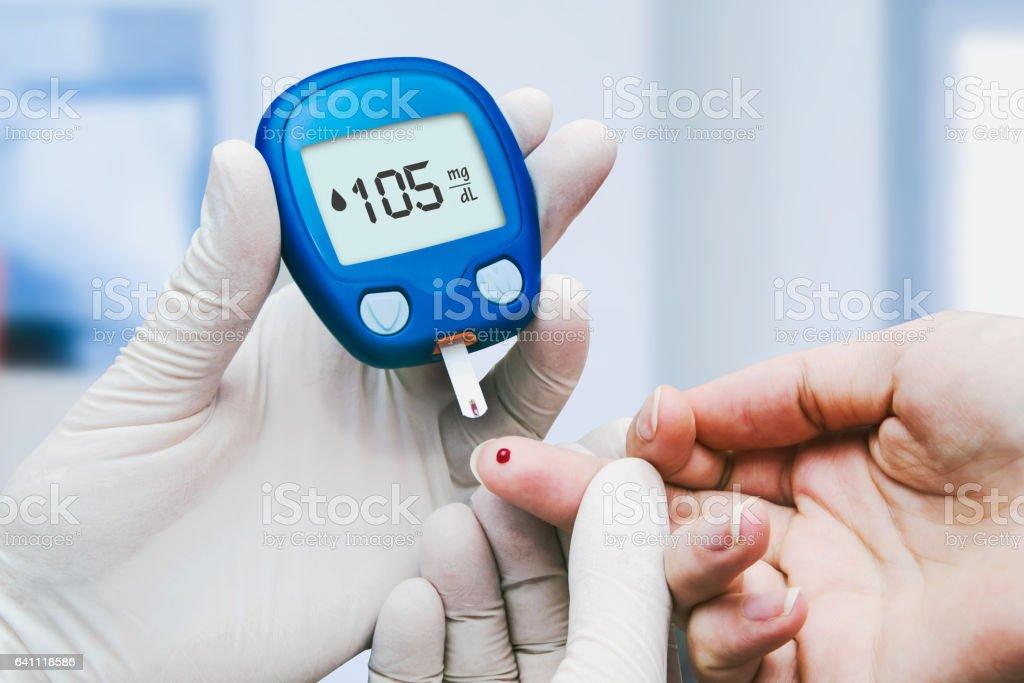 Doctor making blood sugar test stock photo