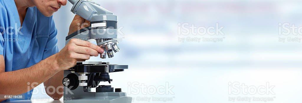 Doctor man with microscope. stock photo