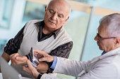 Doctor measuring blood pressure of a senior man.