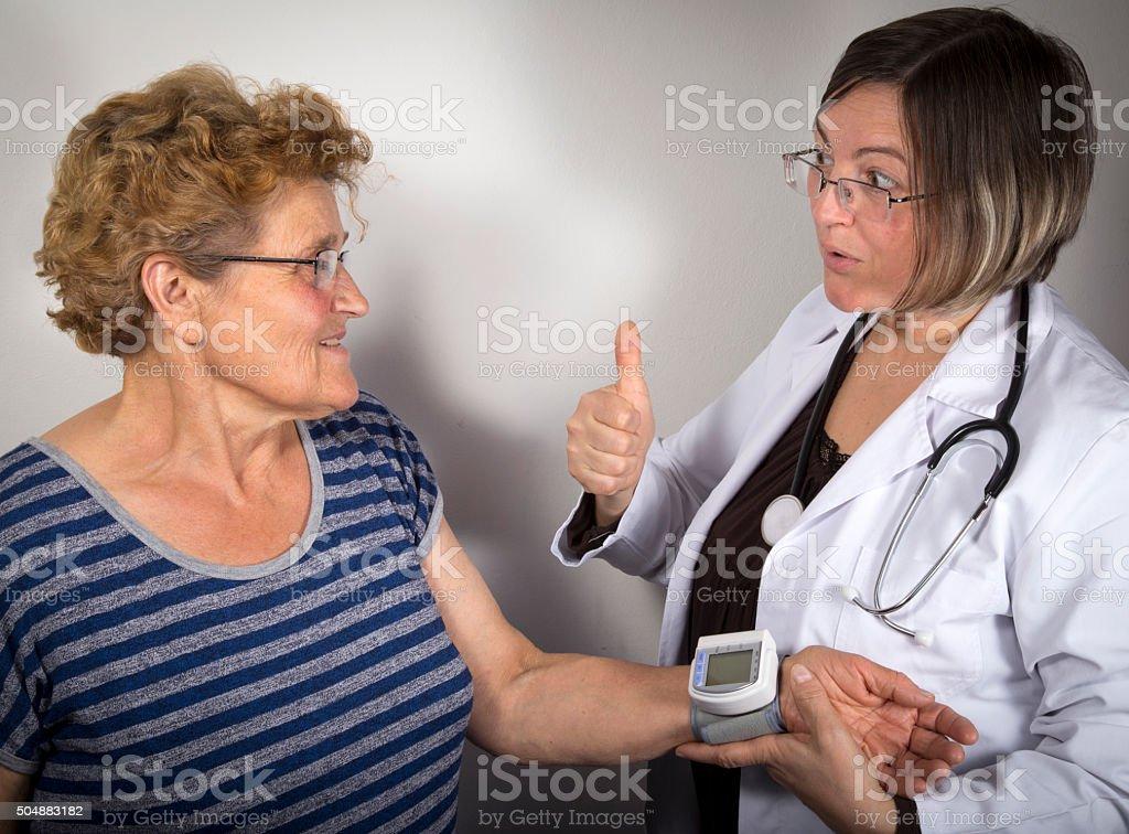 Doctor measuring blood pressure of senior woman royalty-free stock photo