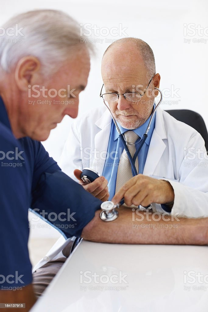 Doctor measuring his senior patient's blood pressure royalty-free stock photo