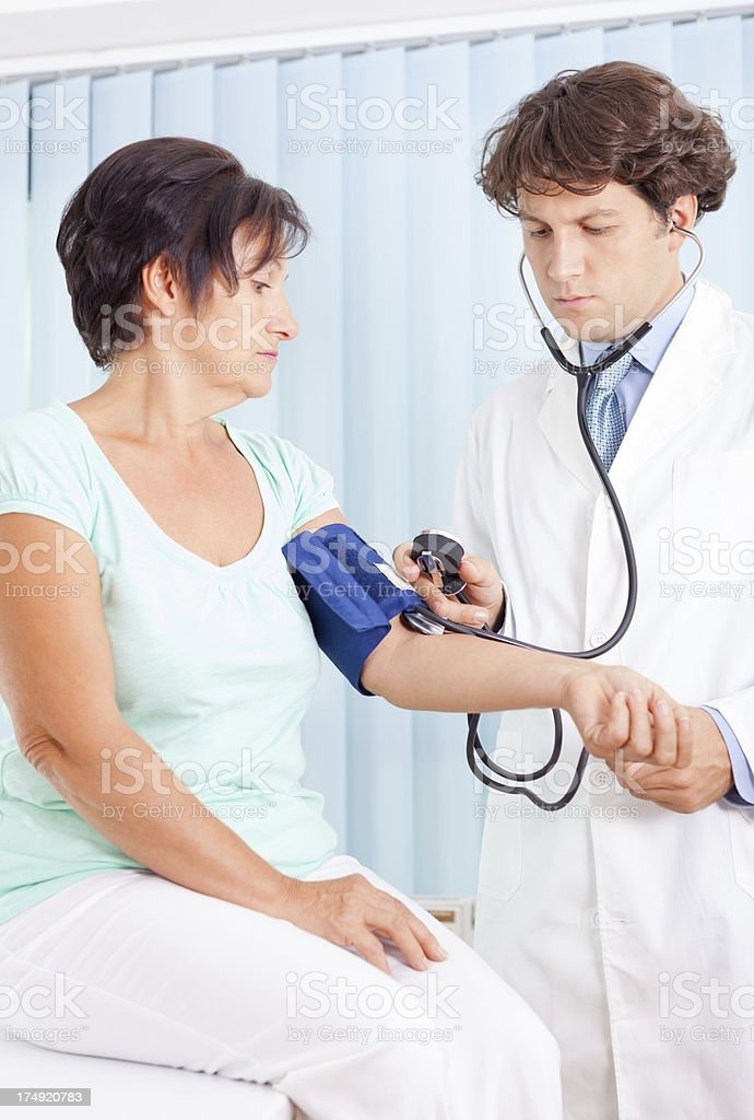 Doctor measuring patient blood pressure royalty-free stock photo