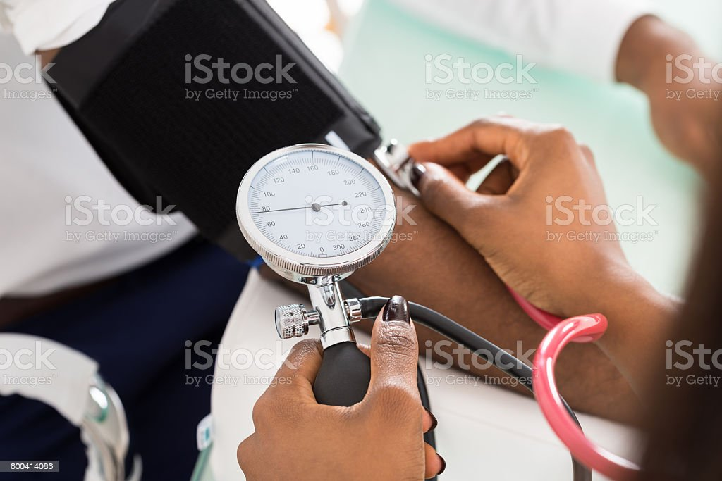 Doctor Measuring Patients Blood Pressure stock photo