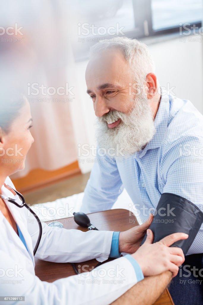 Doctor measuring pressure of patient stock photo