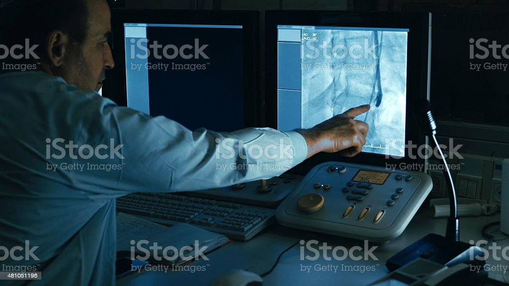 Doctor monitoring injection process into blood vessels stock photo