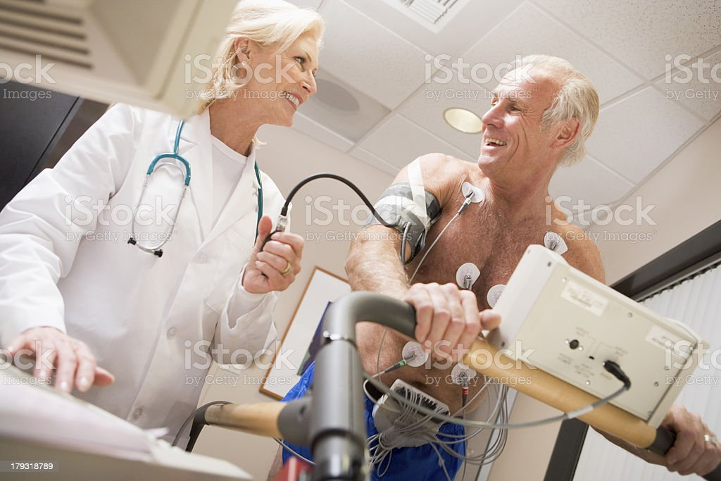 Doctor Monitoring The Heart-Rate Of Patient On A Treadmill royalty-free stock photo