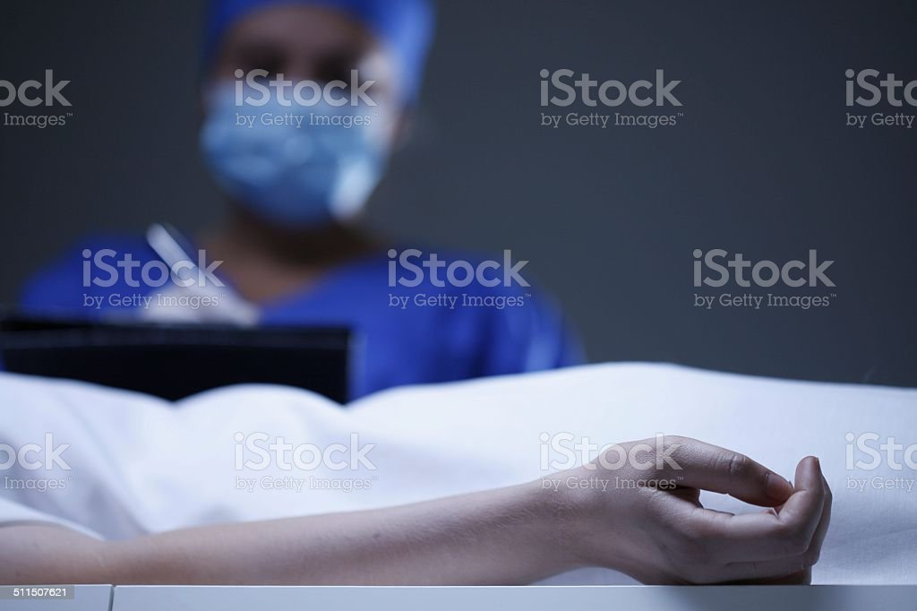 Doctor noting death certificate stock photo