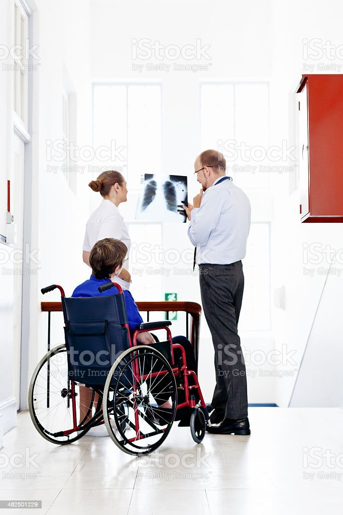 Doctor, nurse, and patient discussing chest X-ray in hospital stock photo