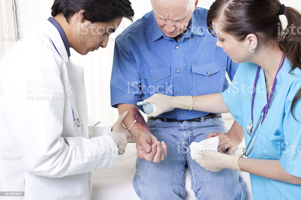 Doctor, nurse treating man's wound, burn.  Emergency room hospital. stock photo