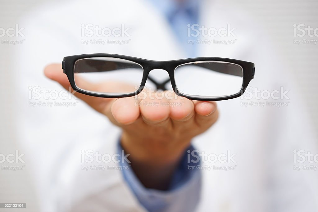 doctor oculist   offering  pair of eyeglasses. concept of good vision stock photo