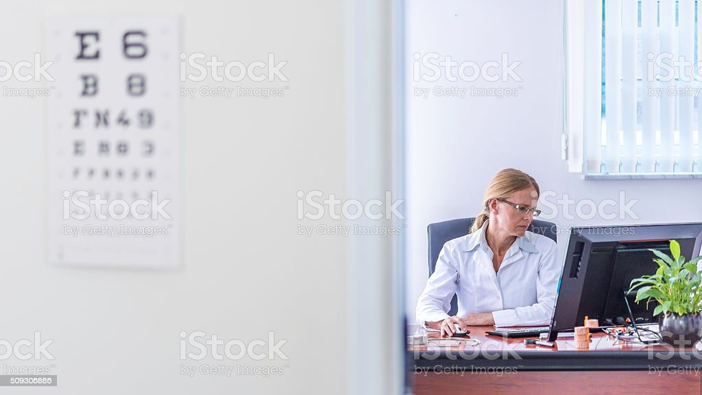 Doctor on the computer in her office stock photo
