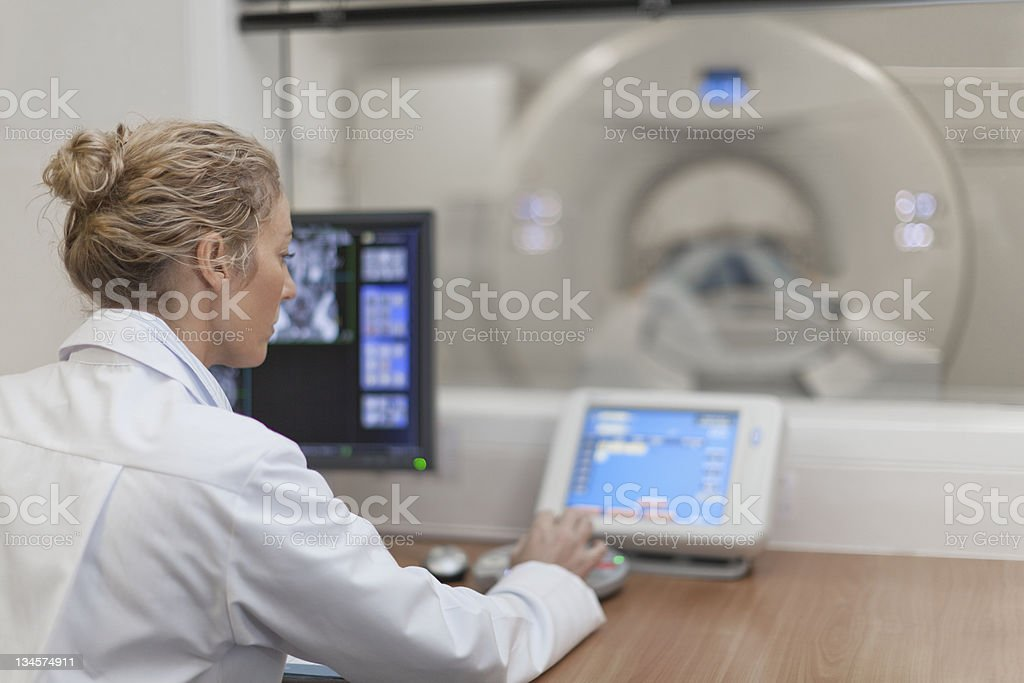 Doctor operating CT scanner in hospital stock photo