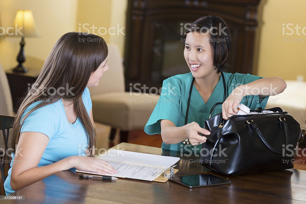 Doctor or midwife treating pregnant patient during housecall stock photo