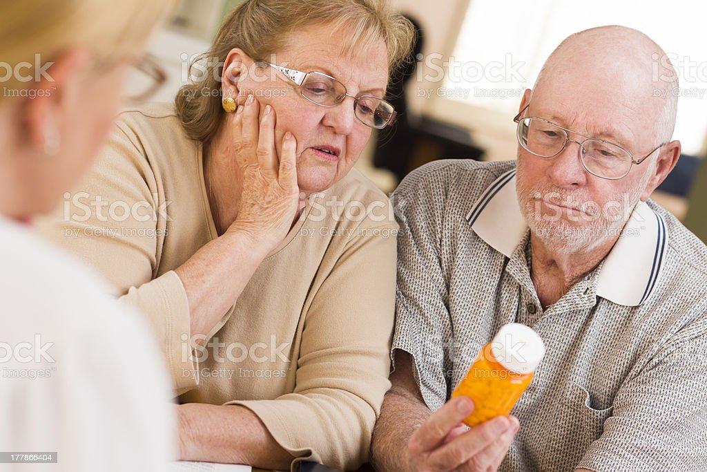 Doctor or Nurse Explaining Prescription Medicine to Senior Coupl royalty-free stock photo