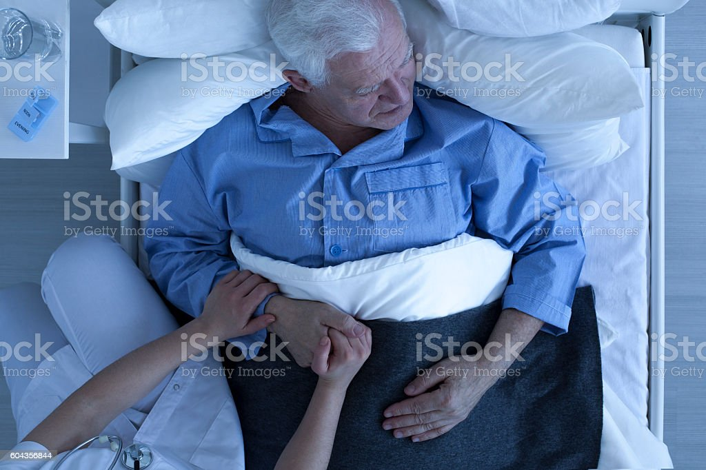 Doctor or nurse holding hand of senior patient stock photo