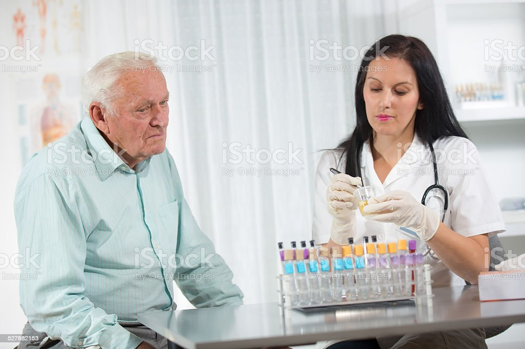 Doctor passes urine cups to patients stock photo