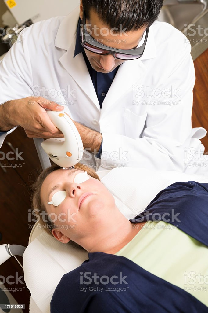 Doctor performing laser skin smothing procedure on a middle-aged woman royalty-free stock photo